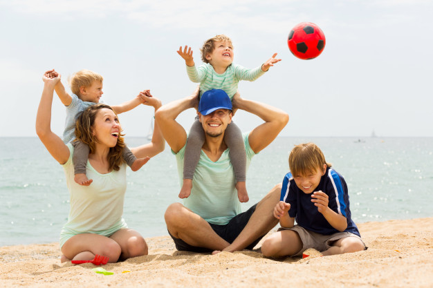 positive-family-of-five-playing-at-sea-beach_1398-4074